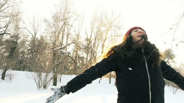 glückliche junge frau spielt mit schnee in superzeitlupe. - schneeflocke sonnenaufgang stock-videos und b-roll-filmmaterial
