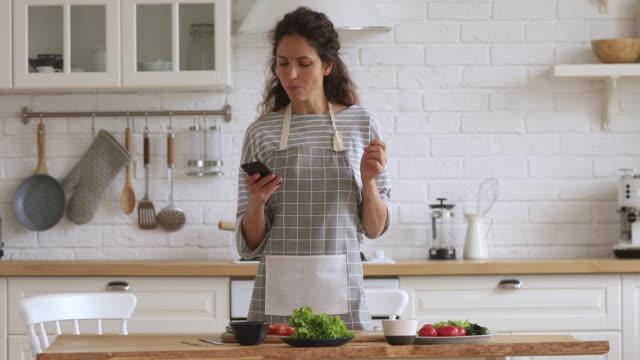 vídeos y material grabado en eventos de stock de feliz joven preparando ensalada de verduras usando la aplicación de libro de cocina móvil - woman cooking