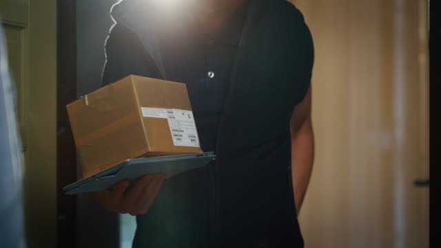 happy young woman receiving and signing a parcel from mailman  delivered in her home - ricevere video stock e b–roll