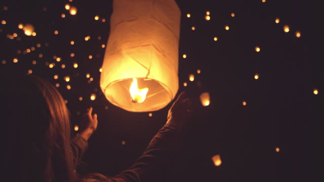 happy young woman releasing lit paper lantern at night  during lantern festival - lanterna attrezzatura per illuminazione video stock e b–roll