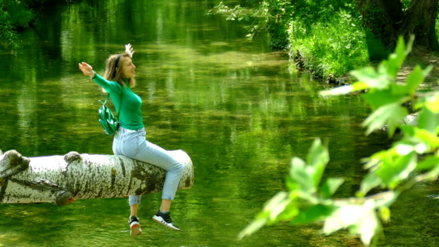 happy young woman resting on a forest river video