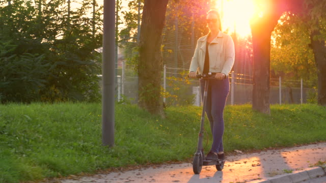lens flare: happy young woman rides an electric scooter on a sunny fall evening. - monopattino elettrico video stock e b–roll
