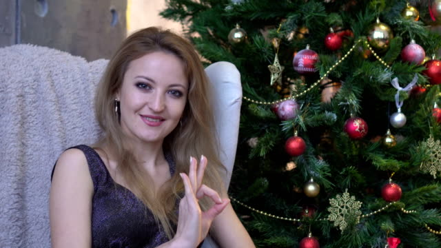 Happy young woman showing ok sign with fingers an winking isolated on a christmas tree background video