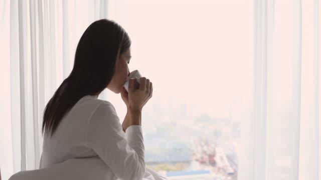 vídeos de stock e filmes b-roll de happy young woman sitting in cozy bed drinking tea - chávena