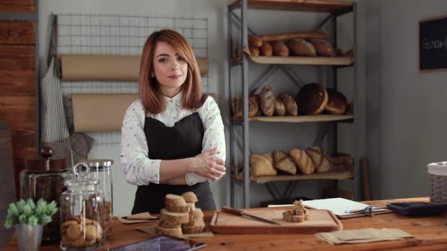 彼女のパン屋さんに自信を持って立っている幸せな若い女 - 上半身点の映像素材/bロール