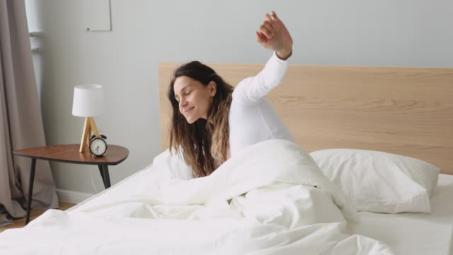 Happy young woman stretching waking up in cozy comfortable bed