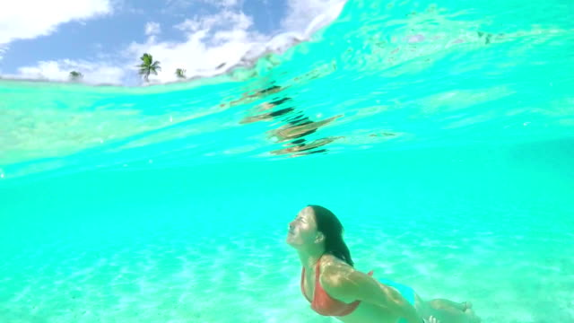 4K SLOW MOTION UNDERWATER CLOSE UP: Happy young woman swimming under the sea and relaxing in crystal clear lagoon in front of beautiful tropical island with exotic beaches and lush palm trees on summer vacation video