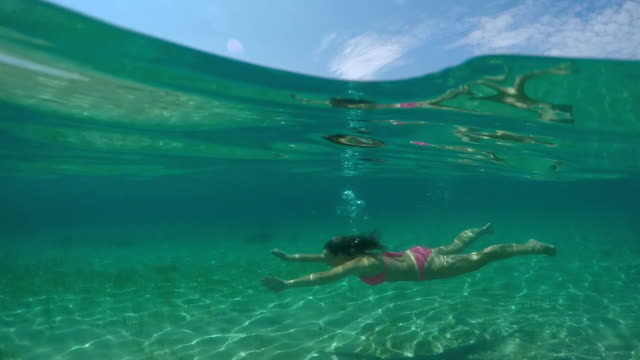 UNDERWATER: Happy young woman swimming underwater and exploring amazing ocean video