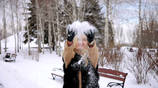 Happy young woman throwing snow in winter park. video