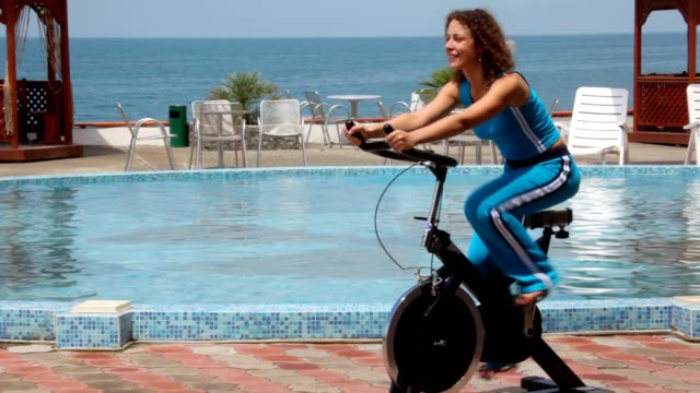 Happy young woman training on exercise bicycle video