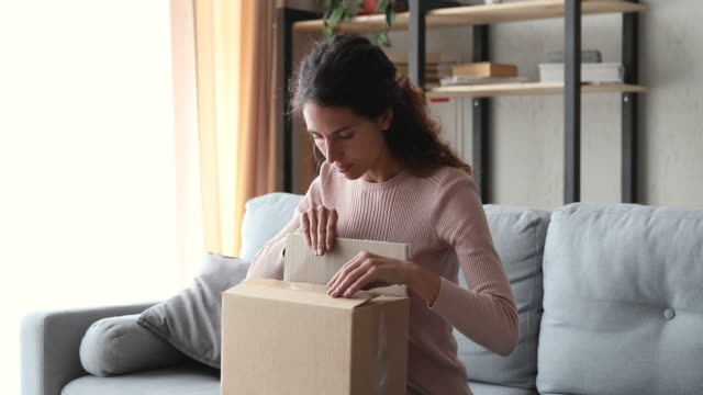 Happy young woman unpacking delivery parcel box at home