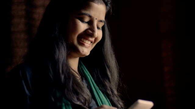 Happy young woman using mobile phone. video