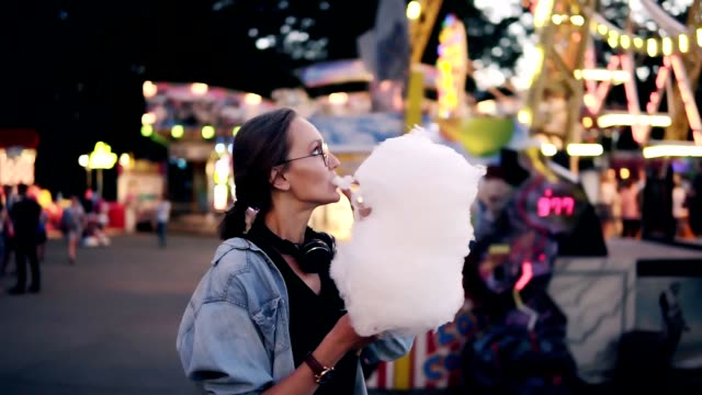 Happy, young woman walking at amusement park in summer. Blonde female eating cotton candy, enjoy her time, smiling Happy, young woman walking at amusement park in summer. Blonde female eating cotton candy, enjoy her time, smiling. cotton candy stock videos & royalty-free footage