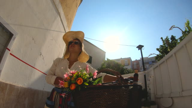 happy young woman walking with vintage bike through colorful traditional old town in ponza island italy. fashion dress colorful skirt - cestino della bicicletta video stock e b–roll
