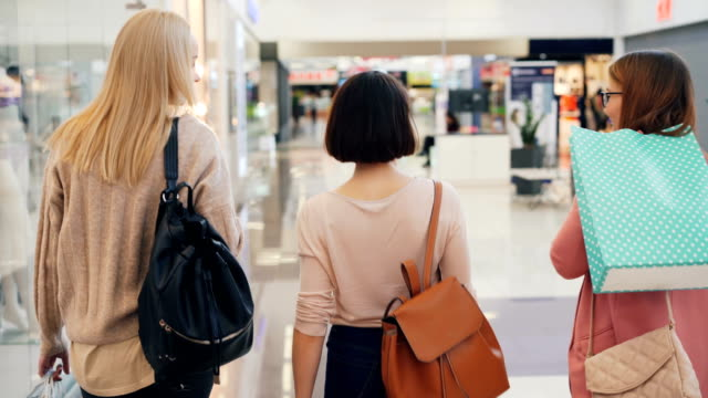 Happy young women friends are walking together in shopping mall holding bright bags and talking at weekend. Communication, youth and friendship concept.