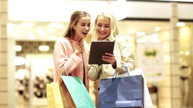 glada unga kvinnor med tabletpc och påsar - köpnarkoman bildbanksvideor och videomaterial från bakom kulisserna