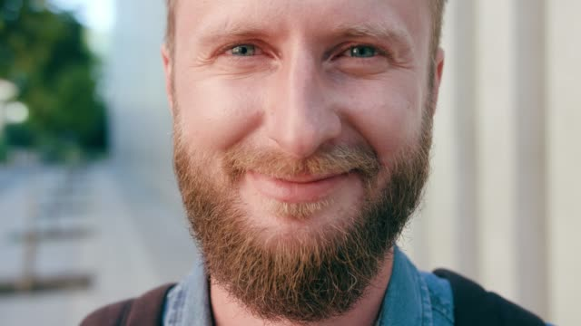 Happyness Smiling Red-Haired Men with Beard in Town A happyness smiling red-haired men with a beard wearing a backpack in the city street. Close-up shot. Soft focus redhead stock videos & royalty-free footage