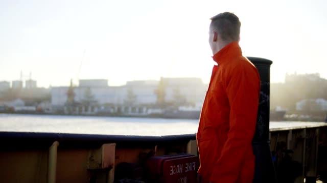 vidéos et rushes de harbor travailleur en orange uniforme debout par le conseil d'administration du navire. lumière parasite. slowmotion - uniforme