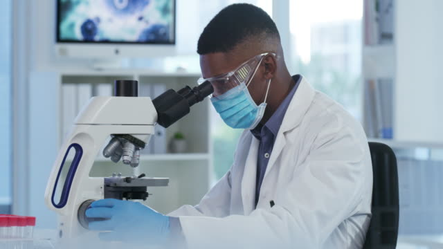 Hard at work 4k video footage of a handsome young medical professional sitting alone and using a microscope in his lab microscope stock videos & royalty-free footage