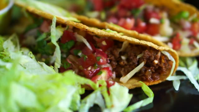 Hard shells beef taco with salsa sauce. Popular Mexican food video