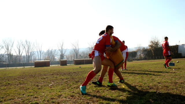 Hard training Young and strong rugby team on the field, group training outdoors. practice drill stock videos & royalty-free footage