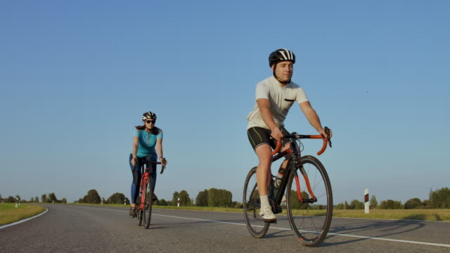 hard training.triathlete two cyclist training on road bicycle. two cyclist riding on road bike in city park and getting ready for triathlon.fit athlete intensive training two man and woman cycling - triatleta video stock e b–roll