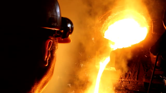 Hard work in the foundry Hard work in the foundry, worker watching and controlling iron smelting in furnaces, too hot and smoky workplace furnace stock videos & royalty-free footage