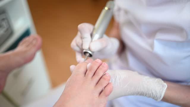 sprzętowy pedicure medyczny z aparatem do ćwiczeń do pilnowania paznokci. pacjent na leczenie pedicure z pediatrą chiropodist. peeling stóp w spa za pomocą specjalnego urządzenia. klinika podiatry podology - pedicure filmów i materiałów b-roll