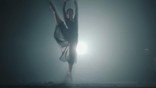 hårt arbetande graciösa ballerina dansa i balett skor och svart klänning i studion - piruett bildbanksvideor och videomaterial från bakom kulisserna