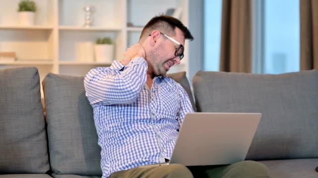 vídeos de stock, filmes e b-roll de homem trabalhador com laptop tendo dor no pescoço em casa - ortopedia