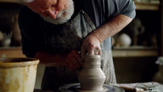 hard-working senior potter is wetting hands in bowl with water and touching clay jar on spinning throwing-wheel. bearded man is concentrated on work. - twórczy zawód filmów i materiałów b-roll