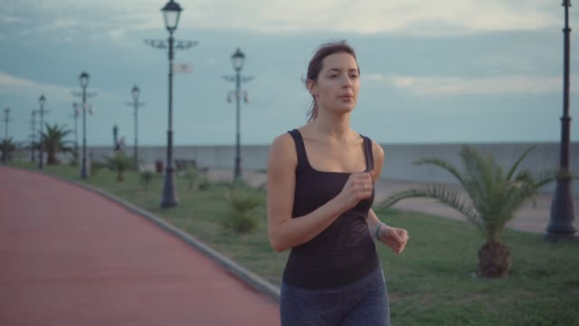 Hardy woman is running alone in park in evening, breathing fresh air