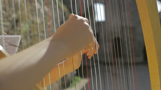 Harp player plays her instrument in a castle in slow motion