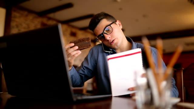 せき立てられたハンサムな青年実業家のラップトップに取り組んでいるガラスのコーヒーを飲み、ケーキを食べ、ノートにメモや検索情報を取って、電話で話しています。マルチタスク telecomuting コンセプト - マルチタスク点の映像素材/bロール