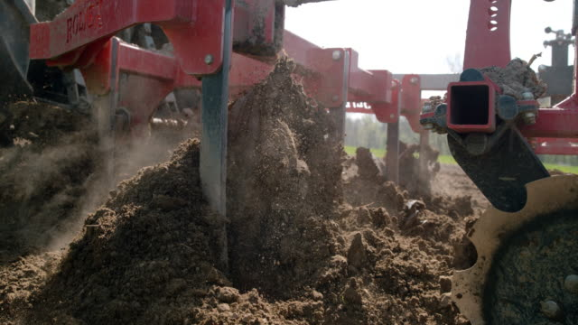 slo mo harrow breaking up and smoothing the soil - trattore video stock e b–roll