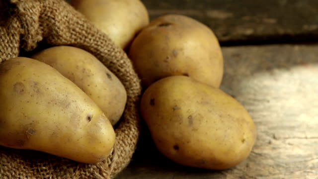 harvested potato put on wooden desk at kitchen - patate video stock e b–roll