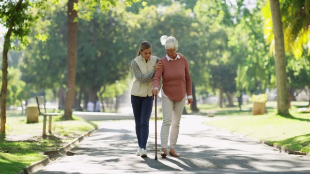 Have the patience they had for you 4k footage of a senior woman using a cane while out for a walk at the park with her daughter crutch stock videos & royalty-free footage