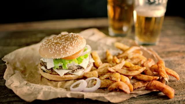 slo mo ds having a double hamburger, crispy potato wedges and beer - cheeseburger filmów i materiałów b-roll