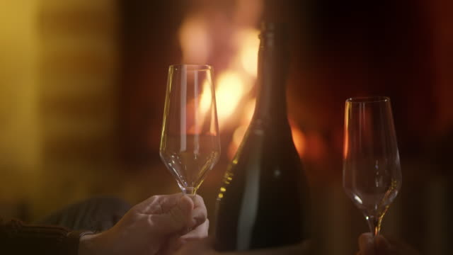 ms having a glass of sparkling wine by the fireplace - date night stock videos & royalty-free footage