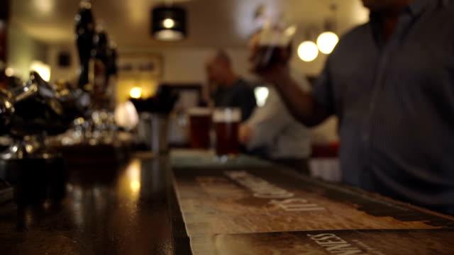having a pint of beer in a british pub - pub bildbanksvideor och videomaterial från bakom kulisserna