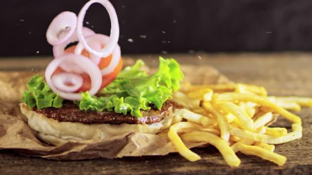vídeos de stock, filmes e b-roll de slo mo ds tendo delicioso hambúrguer e batatas fritas - hamburguer
