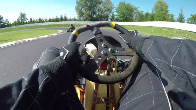 POV: Having fun racing a go kart along a bumpy asphalt racetrack on a sunny day