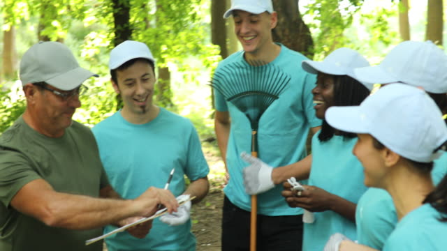 Having fun while cleaning a park Multi-ethnic group of volunteers preparing to clean a public park amputee stock videos & royalty-free footage