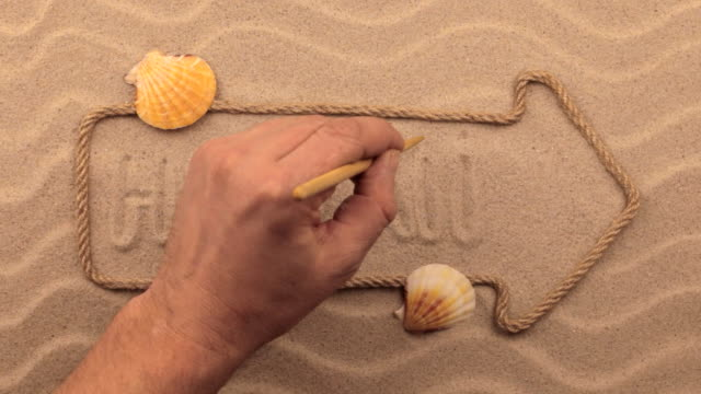 Hawaii inscription written by hand on the sand, in the pointer made from rope. video