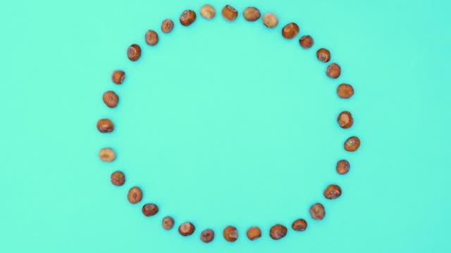 Hazelnut making round frame on green theme. Stop motion