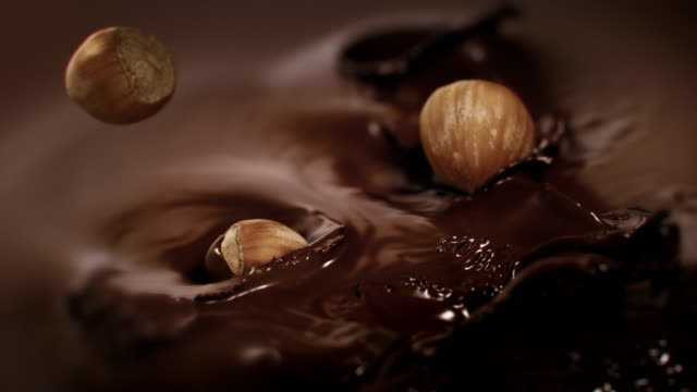 Hazelnuts Splashing Into Liquid Dark Chocolate in 4K Super slow motion
