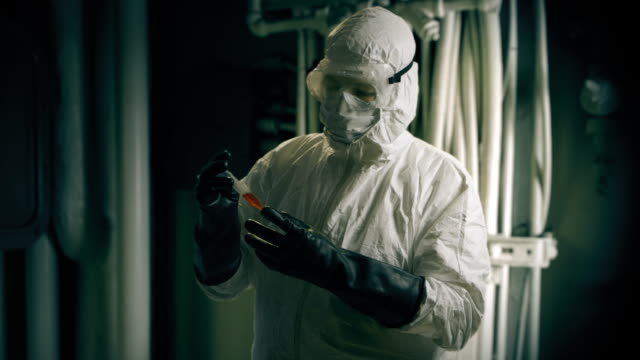 hazmat doctor looking at a blood sample