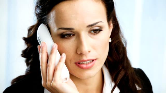 hd1080p: молодая улыбающаяся деловая женщина разговаривает по телефону в офисе - служащая стоковые видео и кадры b-roll