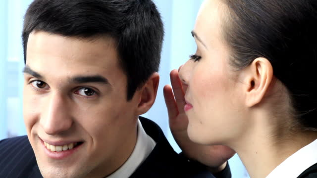 HD1080p30: Two businesspeople telling a secret, tripod. video