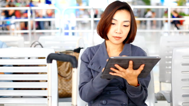 HD:Asian cute women play tablet at the airport. video